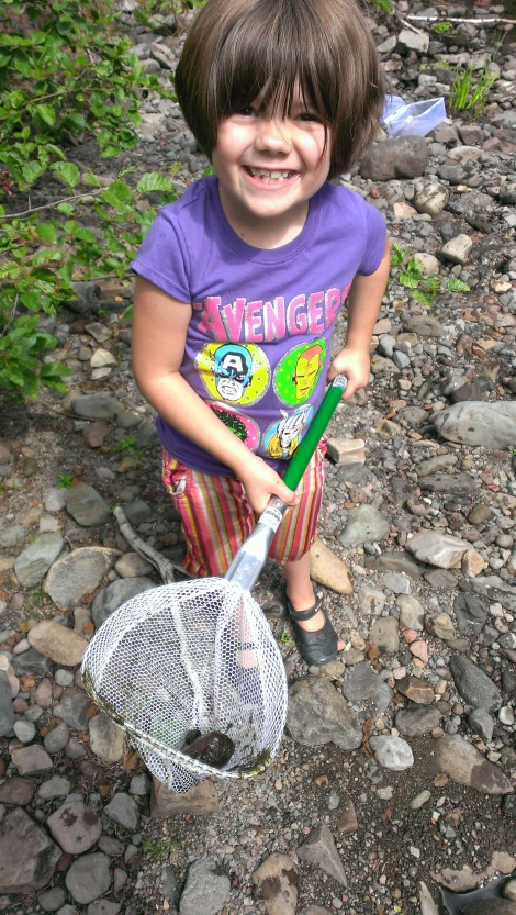 Katy and her net full of rocks and some crane fly larva.  (just little maggots not very attractive to look at)